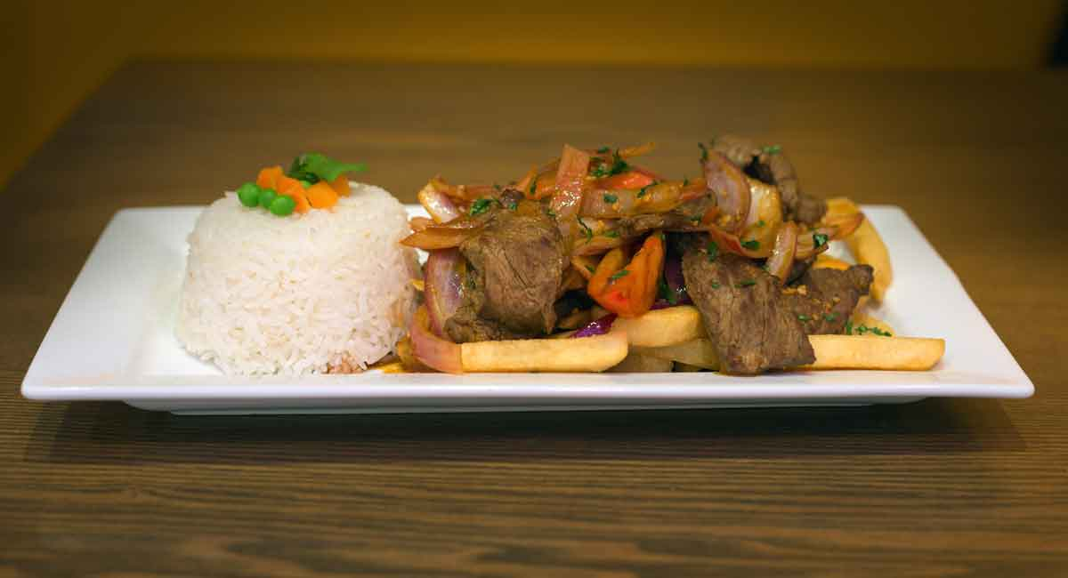Sirloin steak, marinated in aji Amarillo, vinegar, and cilantro; served over French fries, sautéed onions, and white rice